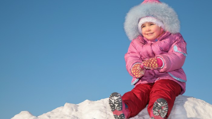 child sit on snow hill on blue sky background 2